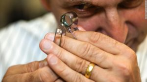 WD Lab Grown Diamonds founder Clive Hill inspects a rough lab-grown diamond
